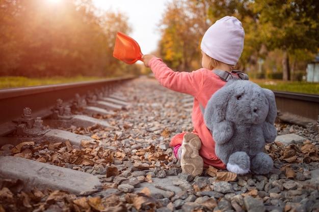 그날 태양의 마지막 광선을 잡는 버려진 철로에서 노는 아이.