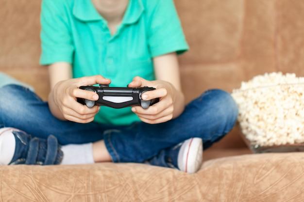 Ребенок играя онлайн видеоигры и есть попкорн сидя на софе в живущей комнате дома. концепция игровых видеоигр