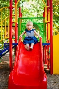 Child playing on outdoor playground. little baby girl plays on school or kindergarten yard