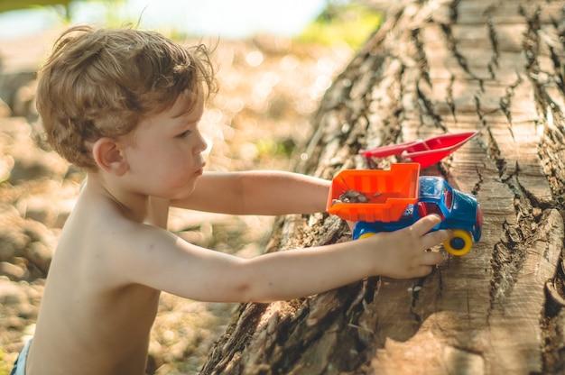 Ребенок играет на открытом воздухе. малыш засыпаем песок в красный грузовик. детские уличные игры. мальчик играет с машиной на большом бревне