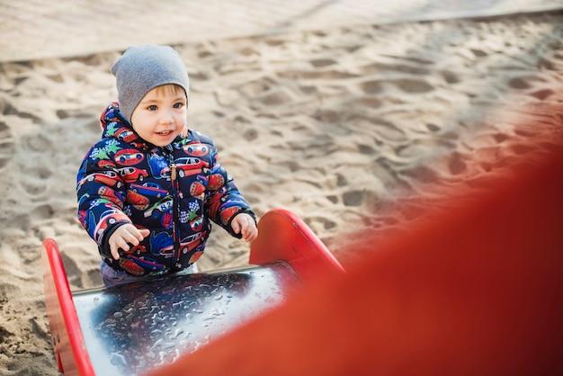 Ребенок играет на улице на детской площадке