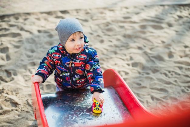 Ребенок играет снаружи на слайде