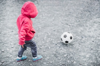 Child playing outside with football