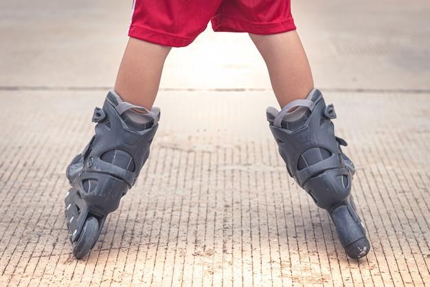 Ребенок играет на роликах в цементной дороге