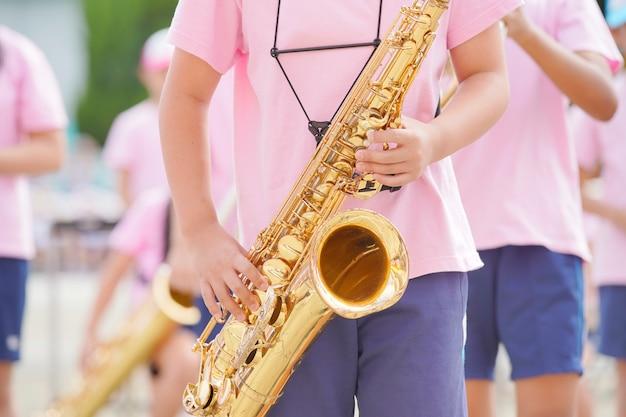초등학교 스포츠의 날에 색소폰을 연주하는 아이