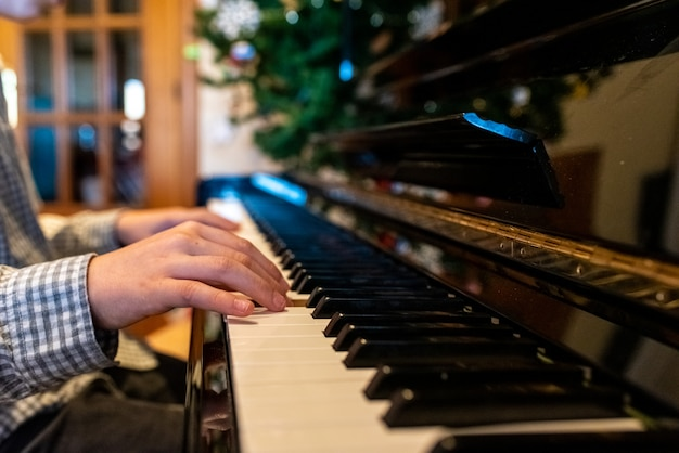 Child playing a song at the piano, closeup of his hands.
