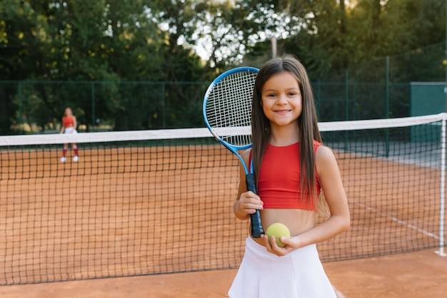 Ребенок играет в теннис на открытом корте. маленькая девочка с теннисной ракеткой и мячом в спортивном клубе. активные упражнения для детей