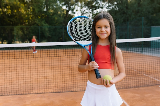 屋外コートでテニスをしている子。テニスラケットとスポーツクラブでボールを持つ少女。子供のためのアクティブな運動