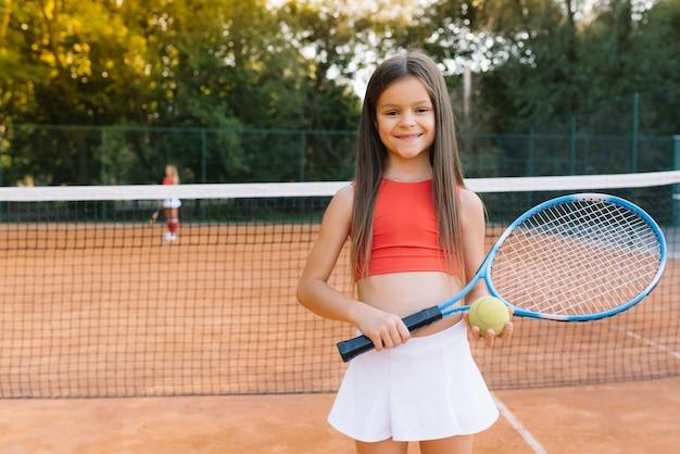 屋外コートでテニスをしている子。テニスラケットとスポーツクラブでボールを持つ少女。子供のためのアクティブな運動 Premium写真