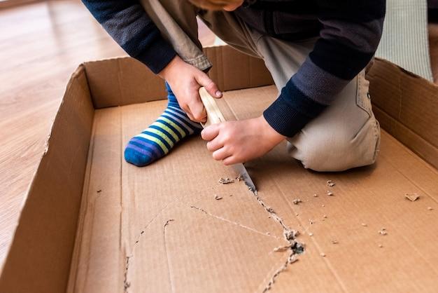 段ボール箱とのこぎりで遊んでいる子供。