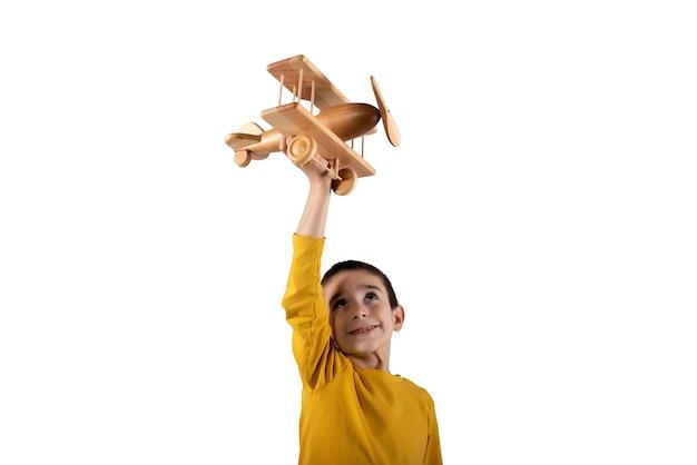 Ребенок играет с маленьким старинным деревянным самолетиком