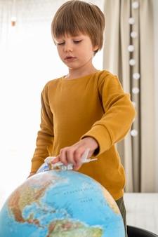 Bambino che gioca con la statuetta dell'aeroplano e il globo