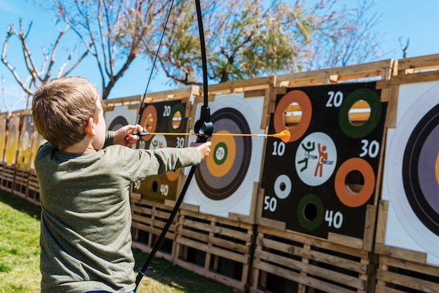 Child playing with a bow and arrows throwing them against a bullseye.