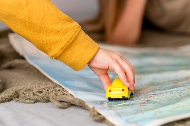 Child playing with car toy on map