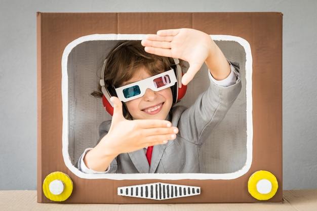 Ребенок играет с картонной коробкой тв. малыш веселится дома. концепция коммуникации