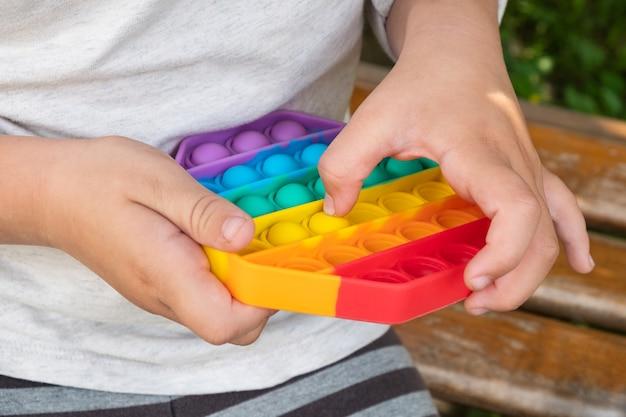Ребенок играет с красочной развивающей игрушкой, простая ямочка