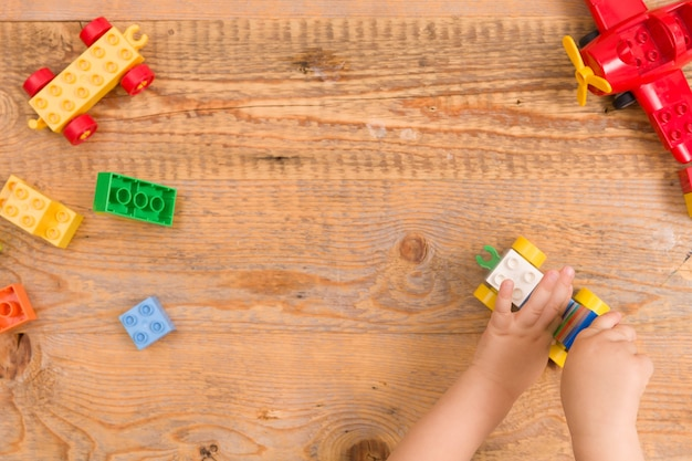 나무 배경에 화려한 장난감 벽돌을 가지고 노는 아이