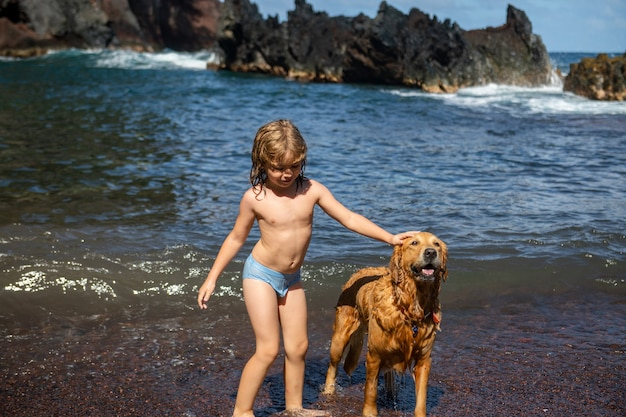 Child playing with dog in sea water on beach.