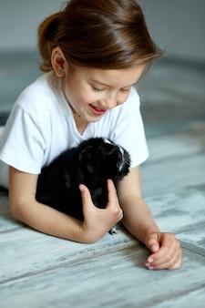 Ребенок играет с морской свинкой. девушка заботится о домашних животных.