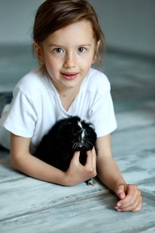 Child playing with guinea pig. girl take care of pets.