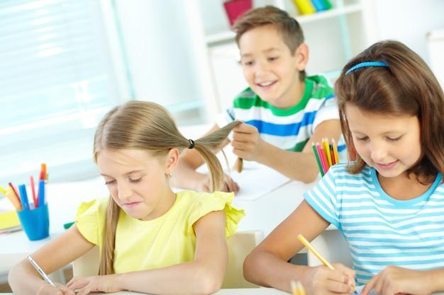 Bambino che gioca con i capelli del suo compagno di classe
