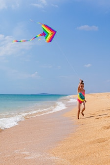 Child playing with a kite while running along the beach, in a summer sunny day.