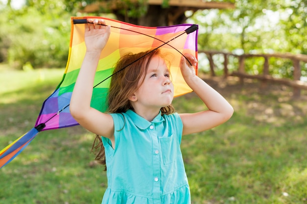 Child playing with a kite while running outdoors, sunset, in summer day.