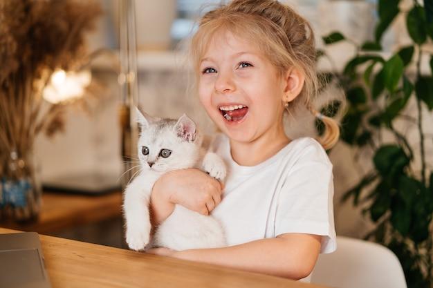 小さな猫と遊ぶ子供。小さな女の子は白い子猫を持っています。