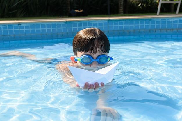 Ребенок играет с бумажным корабликом в бассейне в летний день.