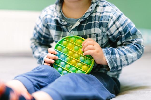 Premium Photo | Child playing with the pop it fidget. rainbow pop it fidget  toy