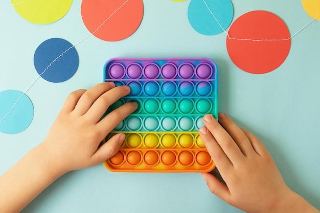 Ребенок играет с радугой pop ittop viewновая игрушка-антистресс для детей