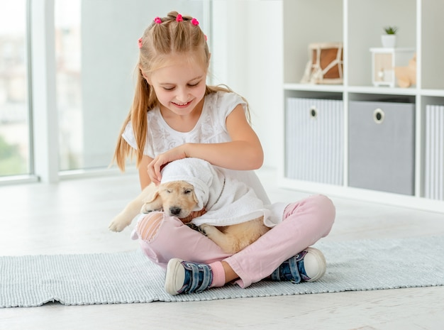 Child playing with retriever puppy