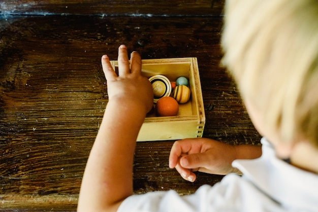 Child playing with small toy planets on an old wooden table.