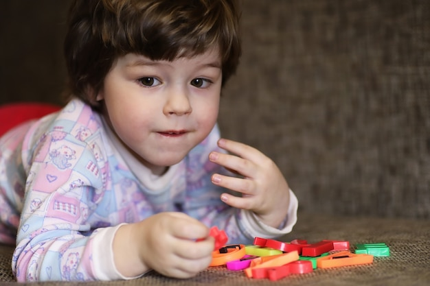 Child playing with small toys on the couch in the room