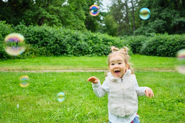 Ребенок играет с мыльными пузырями в парке