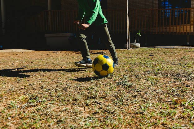 Child playing with a soccer ball in the yard of his house in the sun.