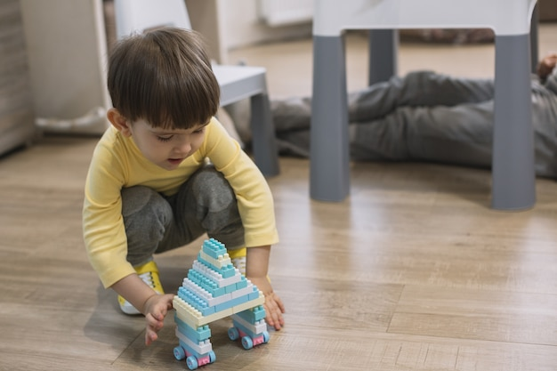 Child playing with toy and father blurred legs