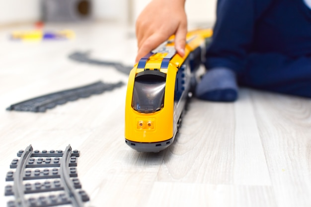 Child playing with toy train on the floor in house