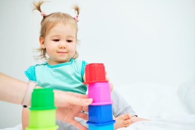 Ребенок играет с игрушками и ее мать