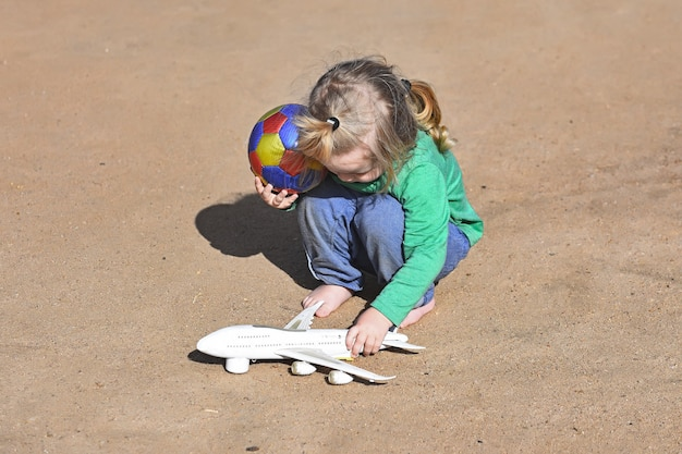 여름 모래 야외의 자연 표면에 흰색 비행기 장난감 및 공을 가지고 노는 아이