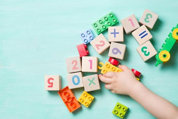 Ребенок играет с деревянными кубиками с цифрами и красочными игрушечными кубиками на бирюзовом деревянном фоне