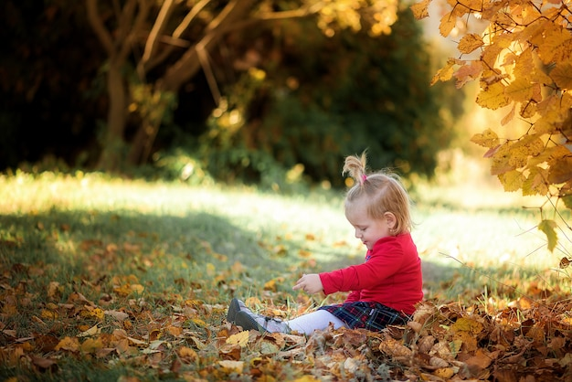 The child plays in the autumn forest with apples and pencils. autumn theme