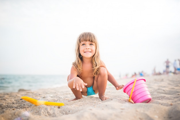 Child plays on beach squatting in sand