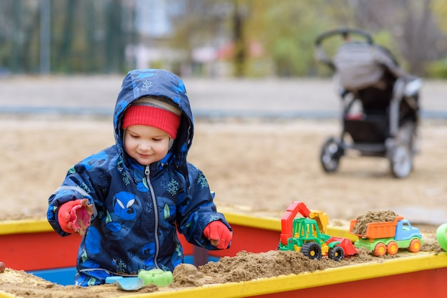 The child plays cars on the playground