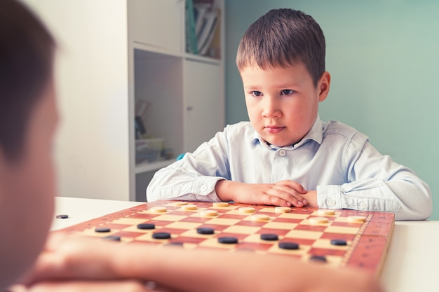 A child plays chess and thinks