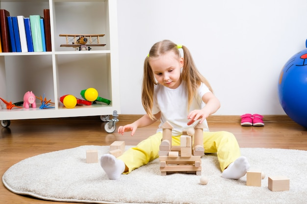 Child plays cubes on the carpet