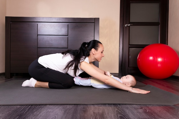 The child plays, does exercises, does gymnastics with his mother at home.