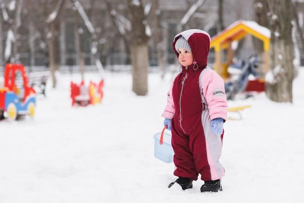 子供は冬に遊び場で遊ぶ