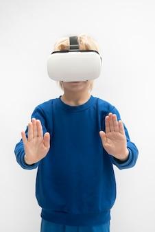 Ребенок играет в игру виртуальной реальности с очками vr. белая стена. вертикальная рама.