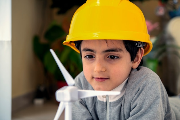 Child plays and looks interested at a wind turbine toy concept future generation